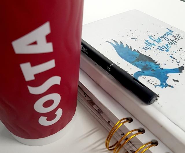 aloma-writes-white-gold-blue-red-black-coffee-mug-pen-desk-notebook.jpg