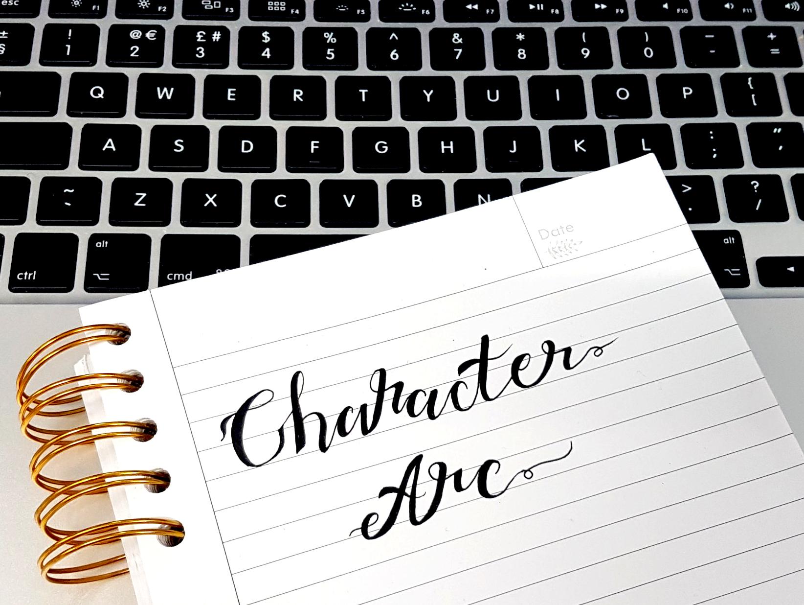 aloma writes character arcs typography notebook laptop keyboard grey gold white black